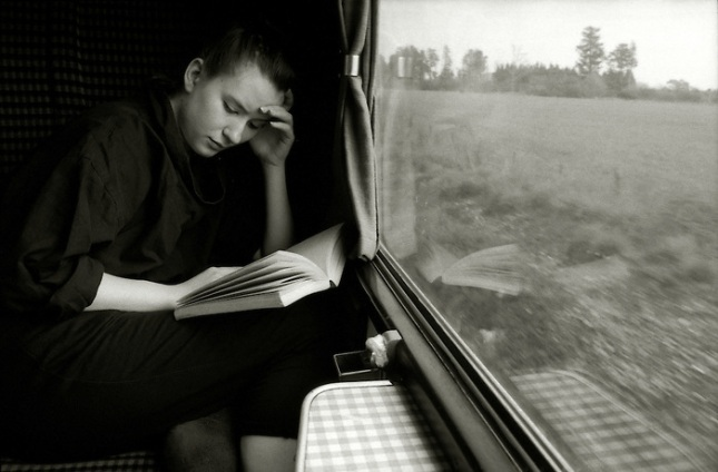 a young woman reading a paperback on a train journey.