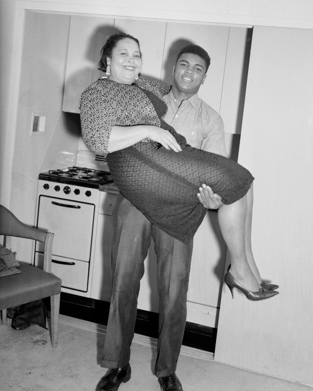 "Mrs. Odessa Grady Clay cradled by her son, The Greatest, Muhammad Ali: photo by Charles ""Teenie"" Harris"